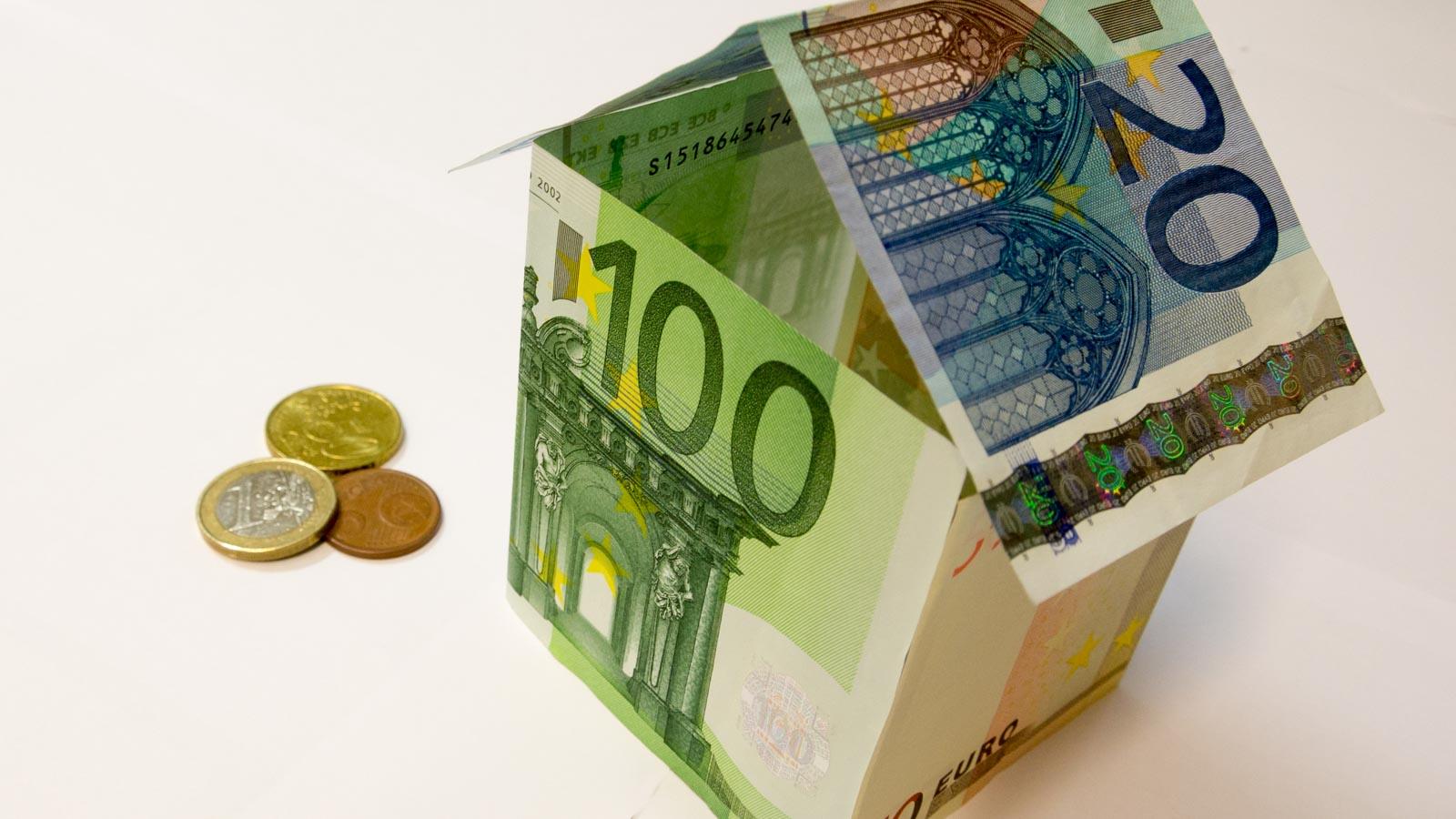 Haus aus Euroscheinen, daneben drei Münzen