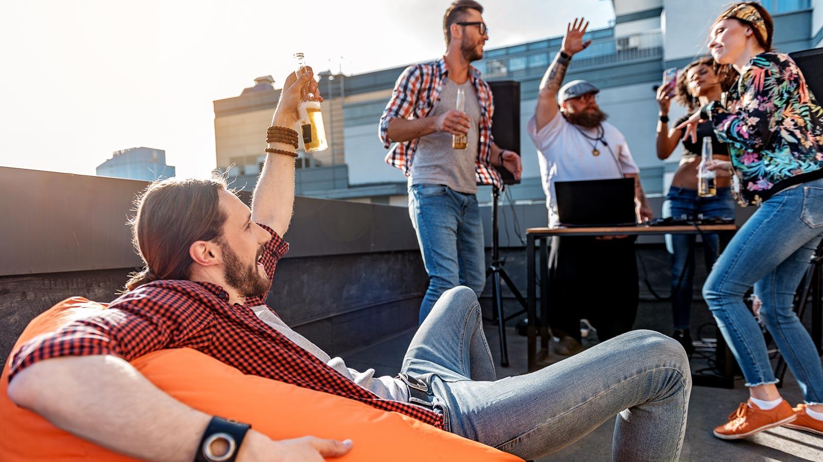 Gruppe junger Leute feiert mit Alkohol und Musik auf einem Balkon