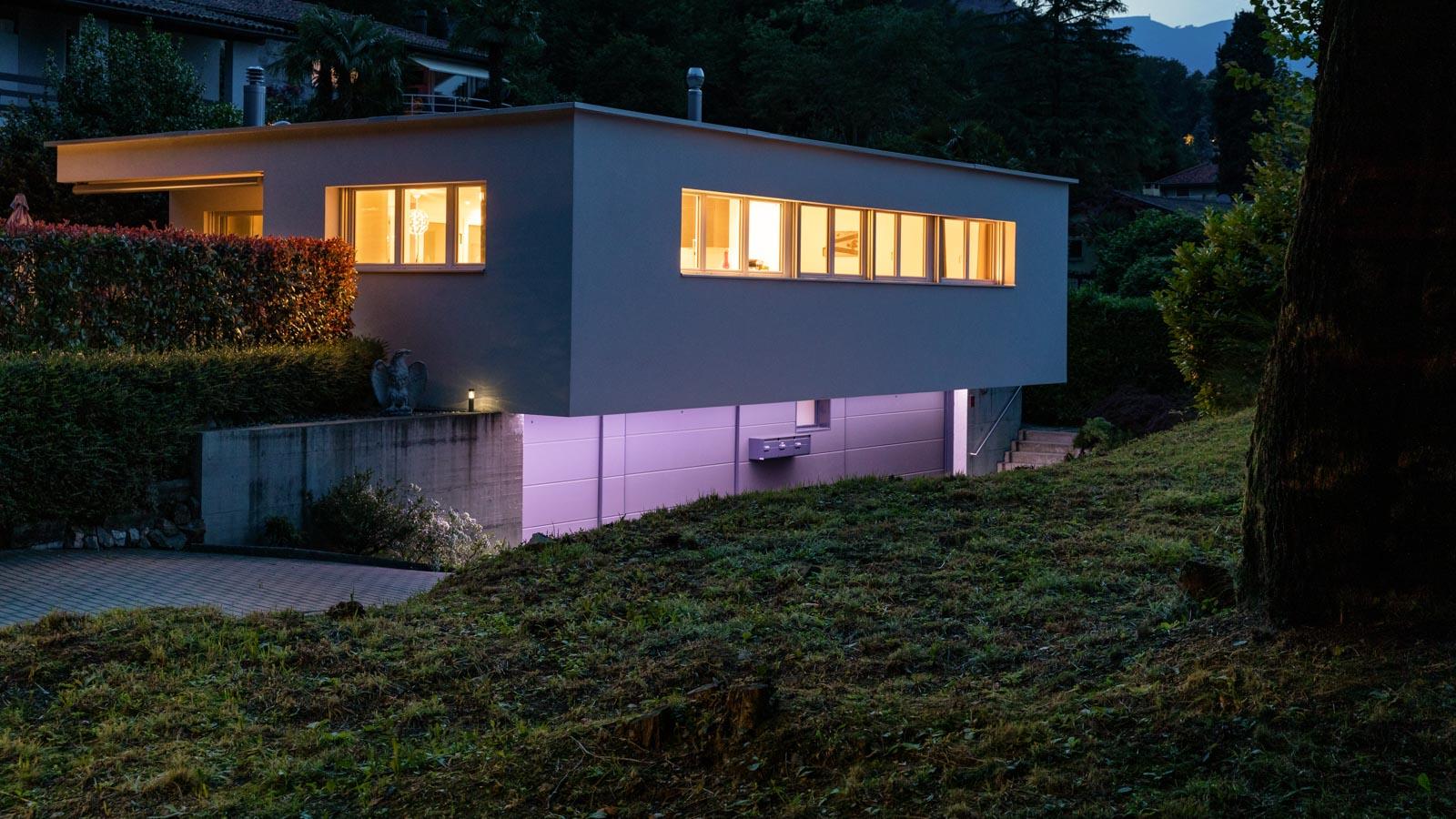 Modernes Haus in der Dämmerung mit farbiger Beluchtung der Zuwege
