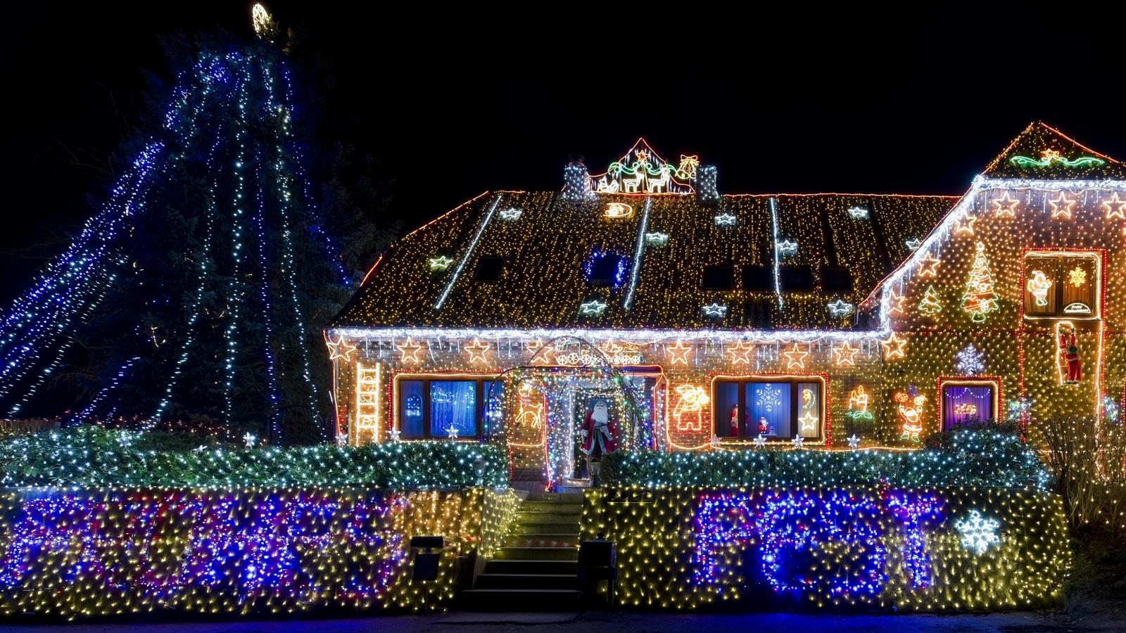 Haus und Garten mit unzähligen Lichtern als Weihnachtsbeleuchtung