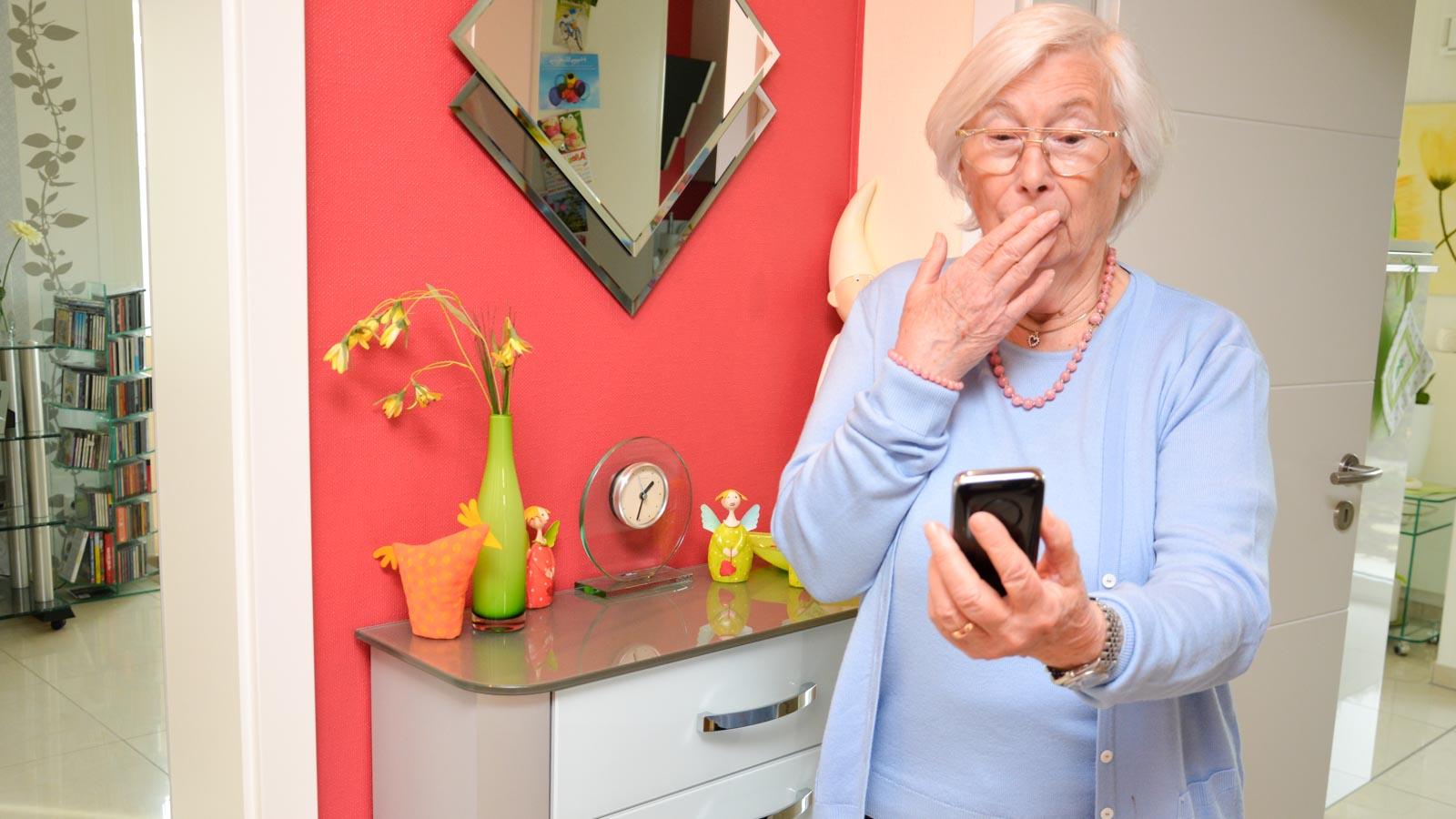 Erschreckte Senioren schaut auf ihr Smartphone