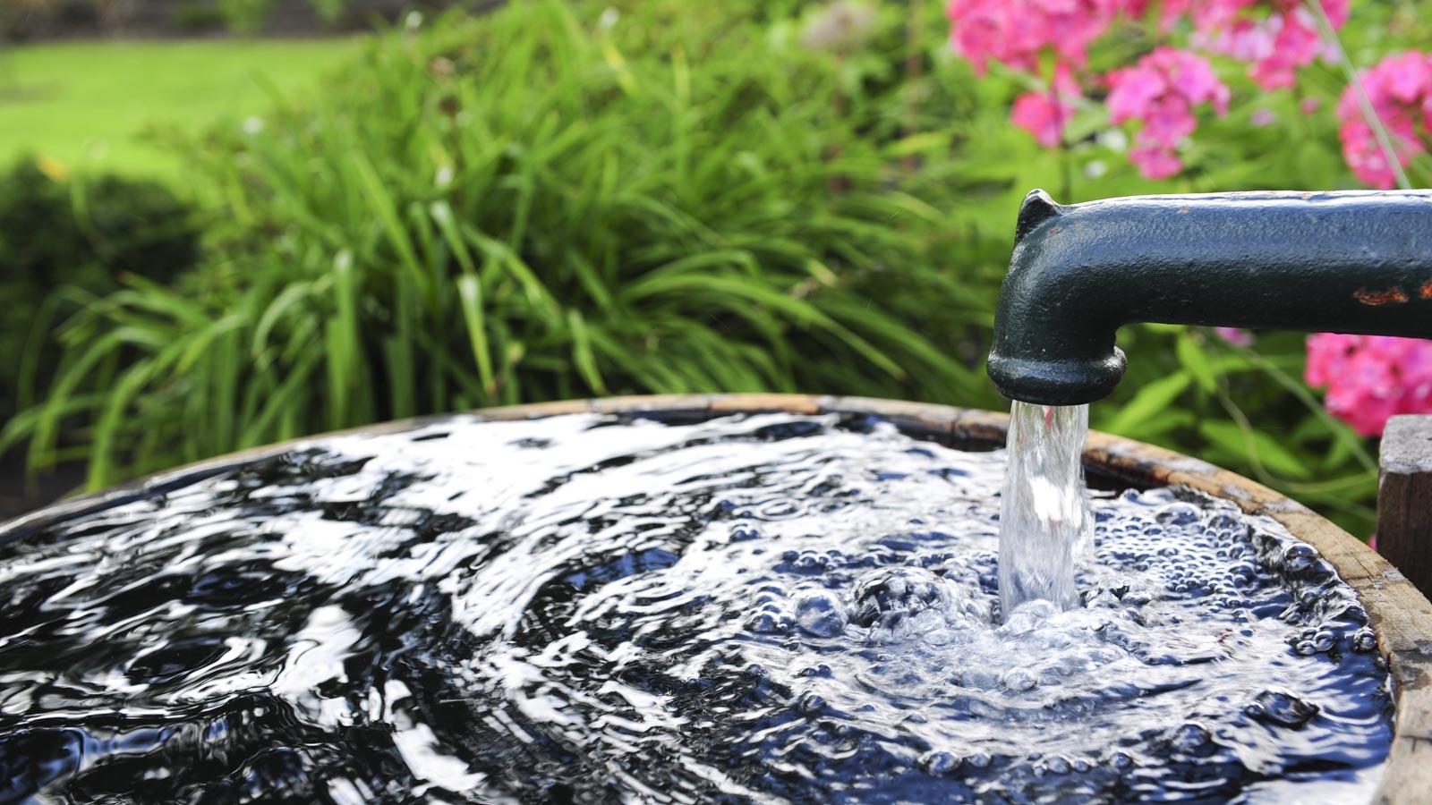 Nahaufnahme eines Gartenbrunnens, in den Wasser fließt