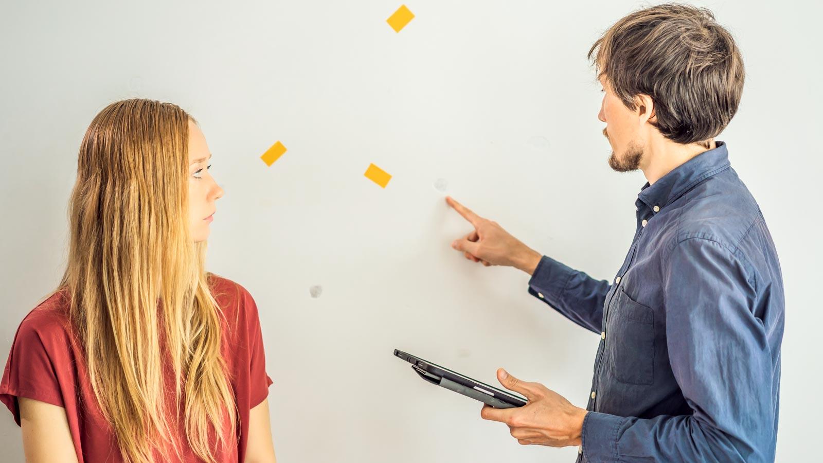 Vermieter zeigt Mieterin zahlreiche Dübellöcher an einer Wand