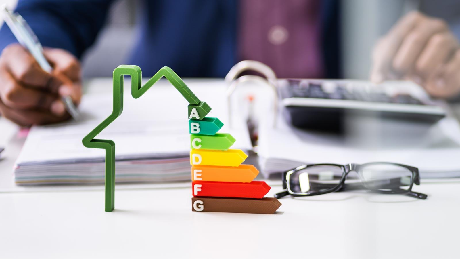 Nahaufnahme mit Hausmodell, Energieeffiziens-Skala, Brille und Person mit Kugenlschreiber, Aktenordner und Taschenrechner