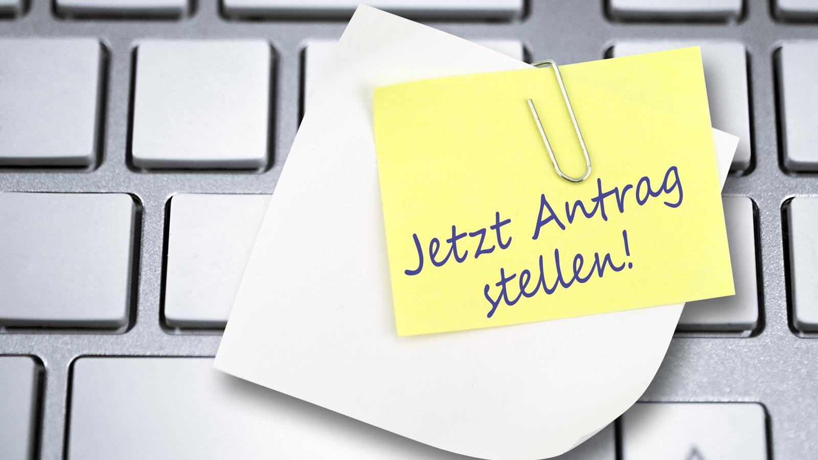 """Tastatur mit angeheftetem Zettel """"Jetzt Antrag stellen"""""""