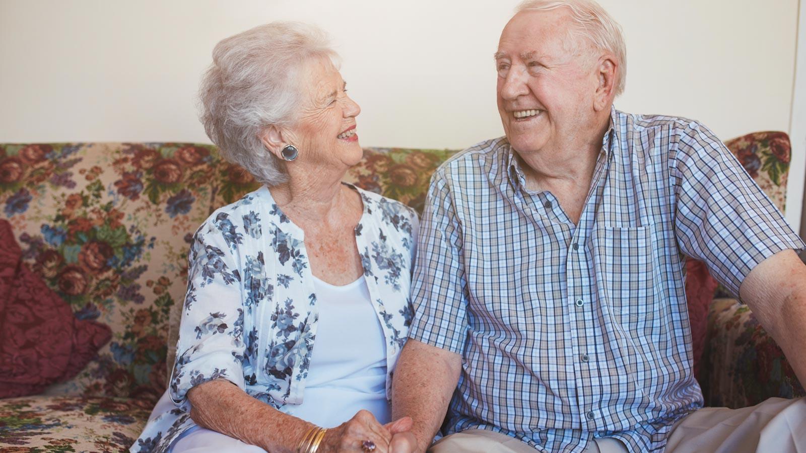Älteres Paar sitzt händchenhaltend auf dem Sofa und lächelt sich an