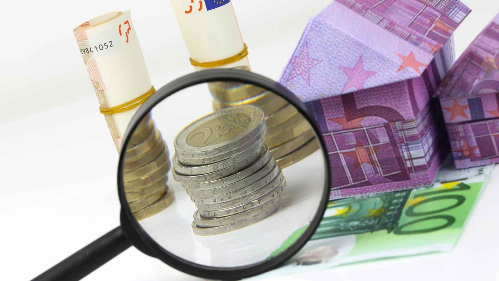 Haus aus Euro-Geldschein, Lupe vergrößert einen Münzstapel