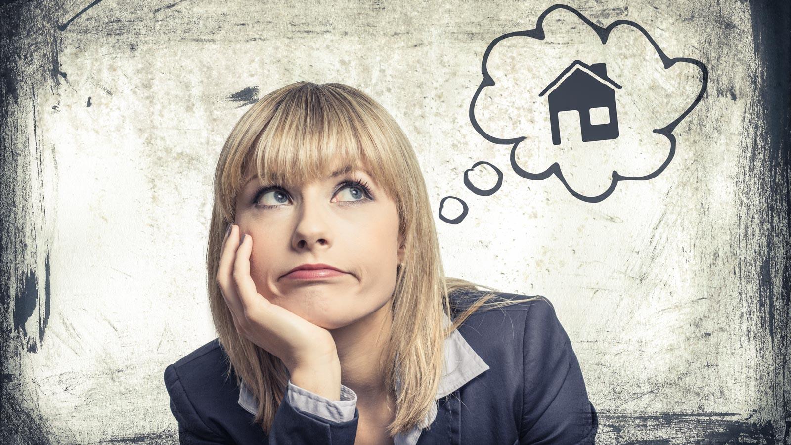 Gelangweilte junge Frau mit Comic-Denkblase, in der ein Haus zu sehen ist
