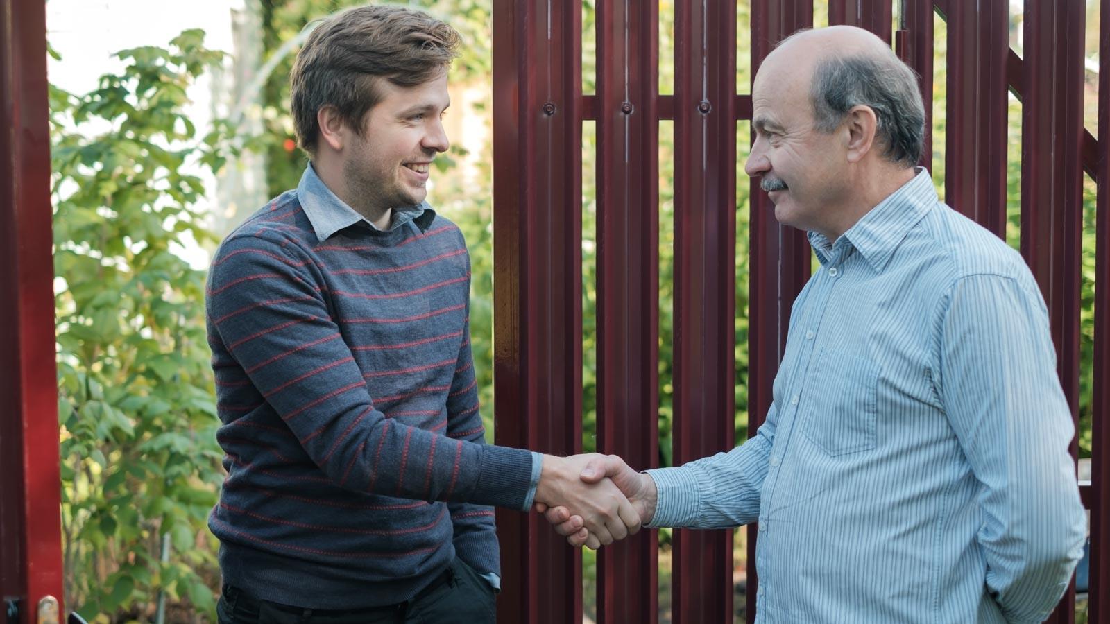 Ein älterer und ein jüngerer Mann reichen sich am Gartentor lächelnd die Hand