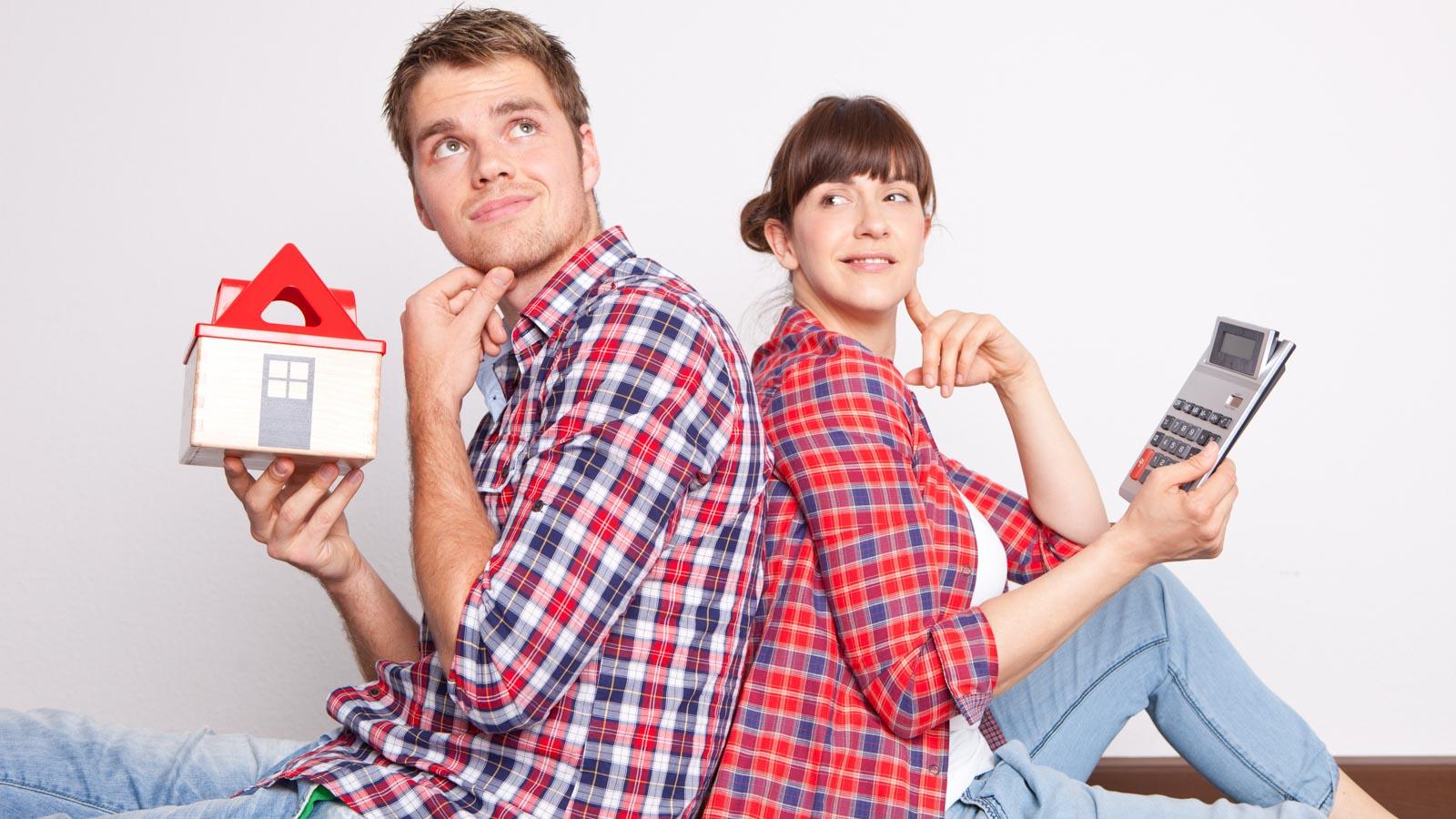 Junges Paar sitzt Rück an Rücken, Mann mit Modellhaus, Frau mit Taschenrechner in der HAnd