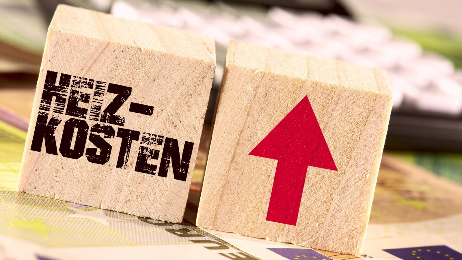 """Zwei Holzwürfel auf Geldscheinen: Einer mit der Aufschrift """"Heizkosten"""", daneben einer mit einem nach oben weisenden roten Pfeil."""