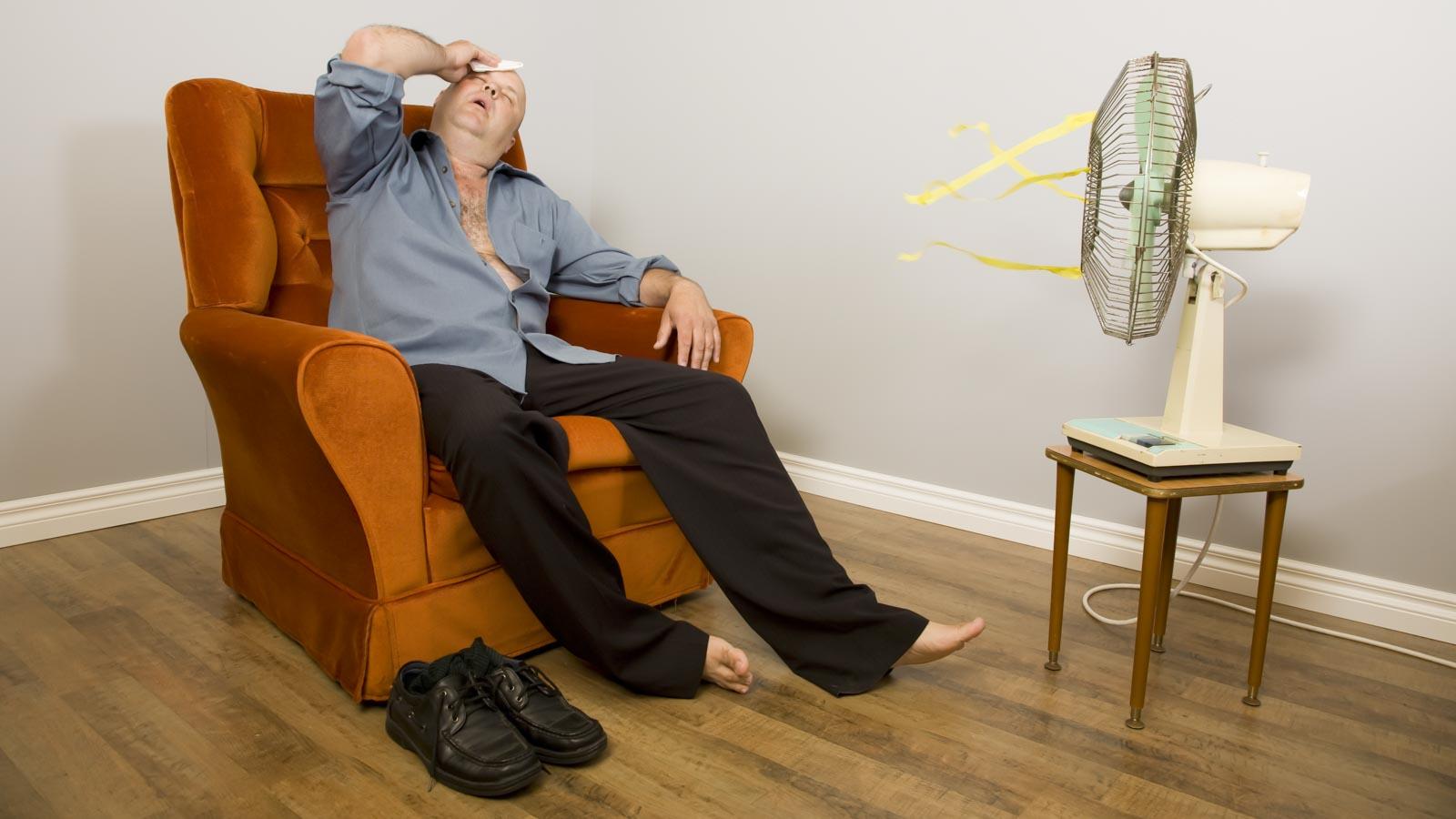 Mann auf einem Sessel sitzt vor einem Ventilator und leidet unter der Hitze im Raum