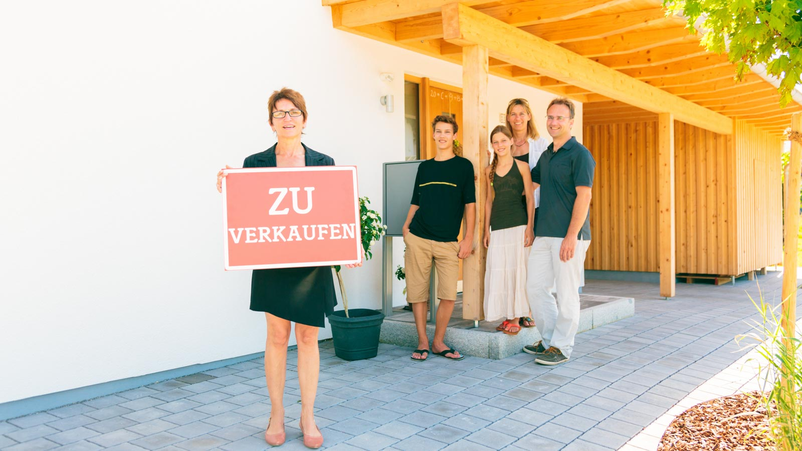 Maklerin mit ZU verkaufen-Schild vor einer jungen Familie am Hauseingang