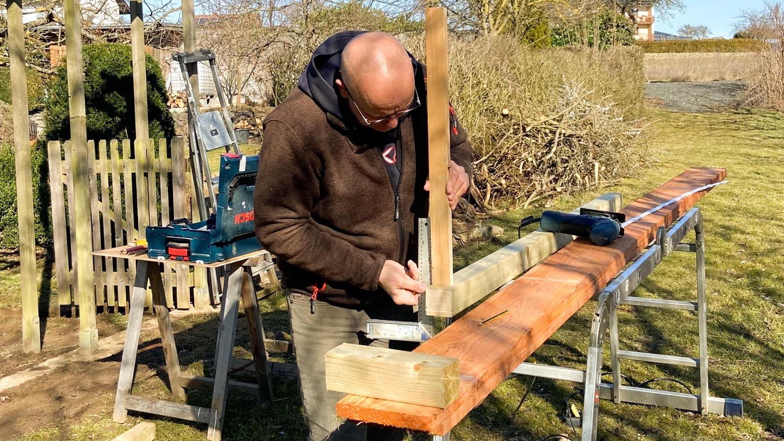 Gartenberater Martin Breidbach beim Zuschnitt von Holzleisten für einen Hühnerstall