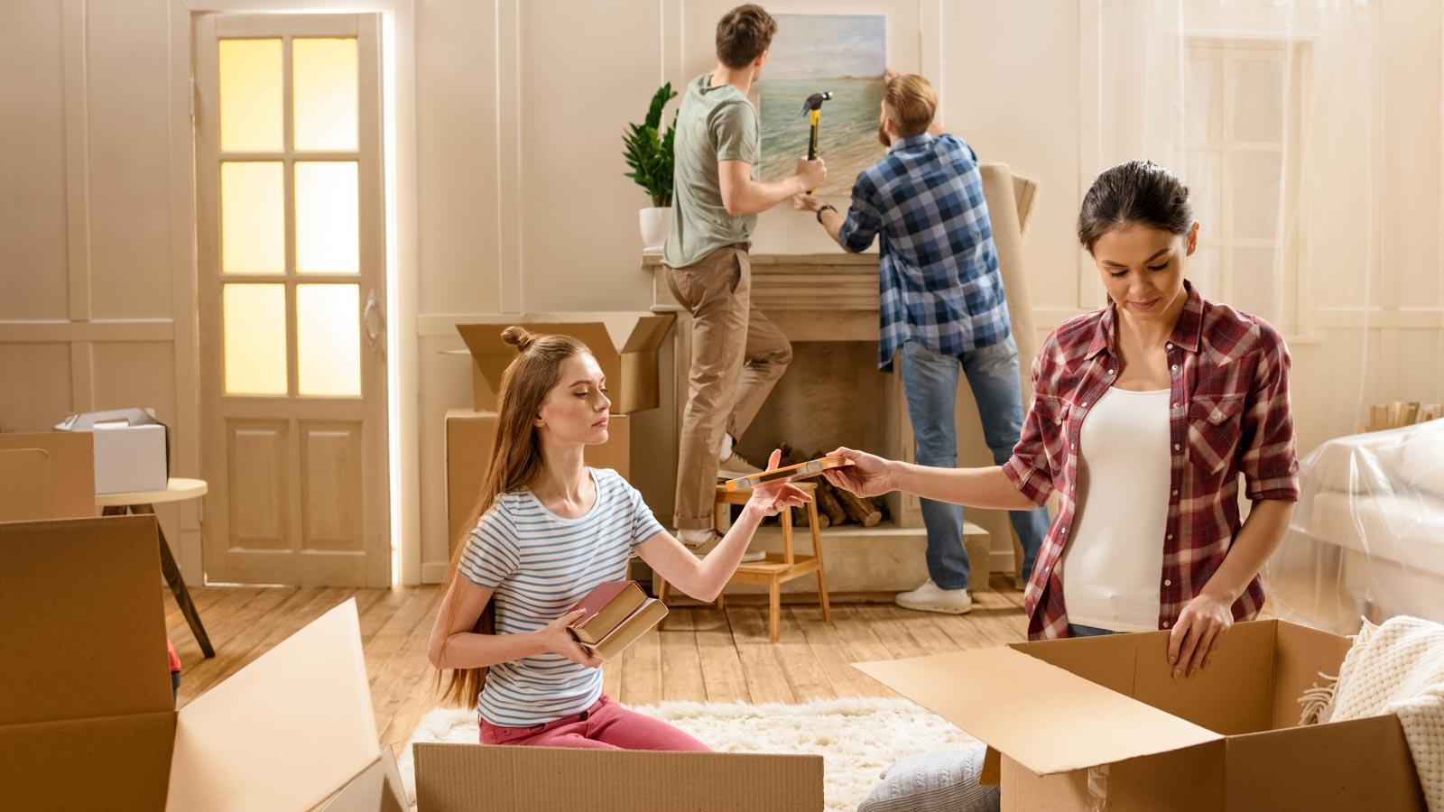Freunde helfen sich beim Umzug: Zwei junge Frauen packen Bücher iin Karton, zwei junge Männer hängen ein Bild an die Wand.