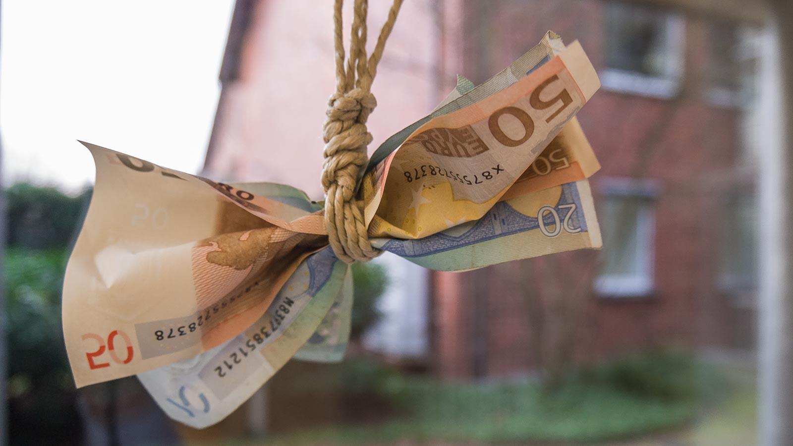 Euroscheine an einem Seil verknotet vor einem Wohnhaus im Hintergrund