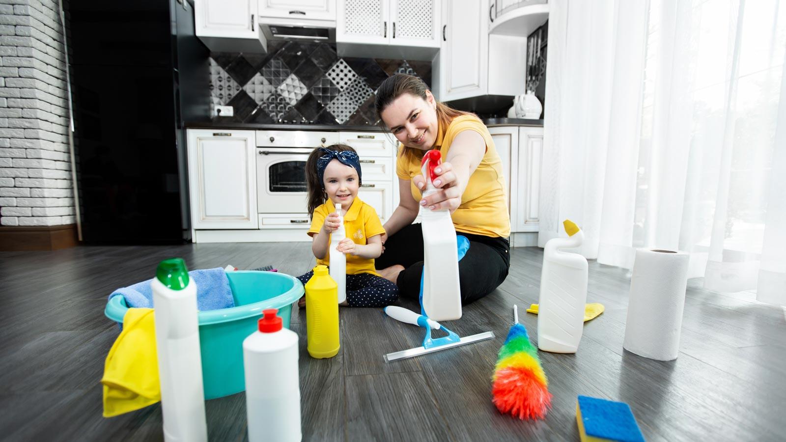 Mutter und Kind mit Putzmitteln kniend vor eine Küche