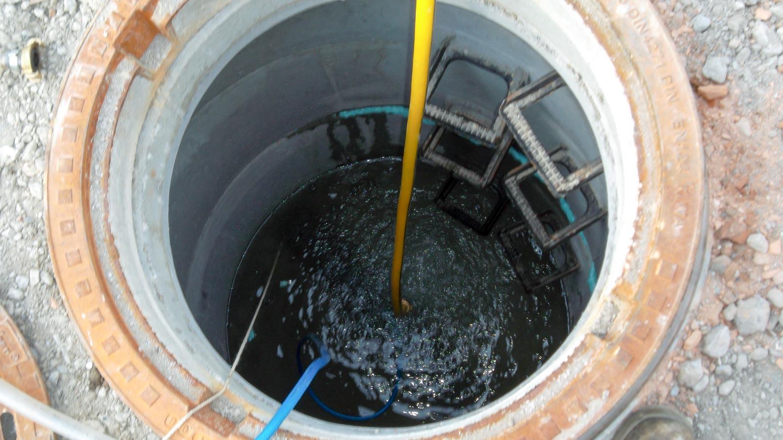 Blick von oben in einen geöffneten Abwasserkanal