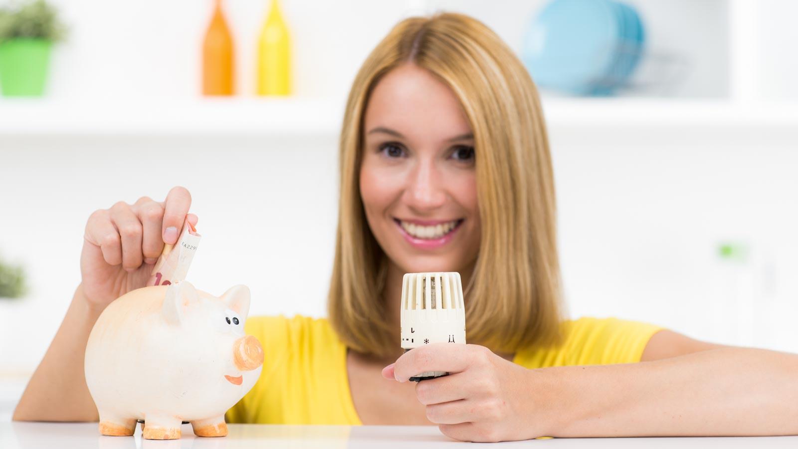 Lächelnde junge Frau mit Heizungsthermostat in der Hand steckt Geldschein in ein Sparschwein