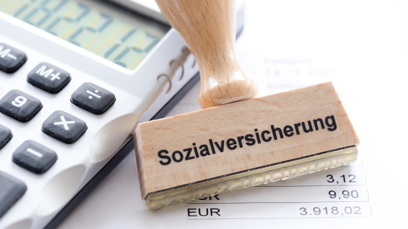 Stempel mit der Aufschrift Sozialversicherung neben Taschenrechner und Gehaltsabrechnung