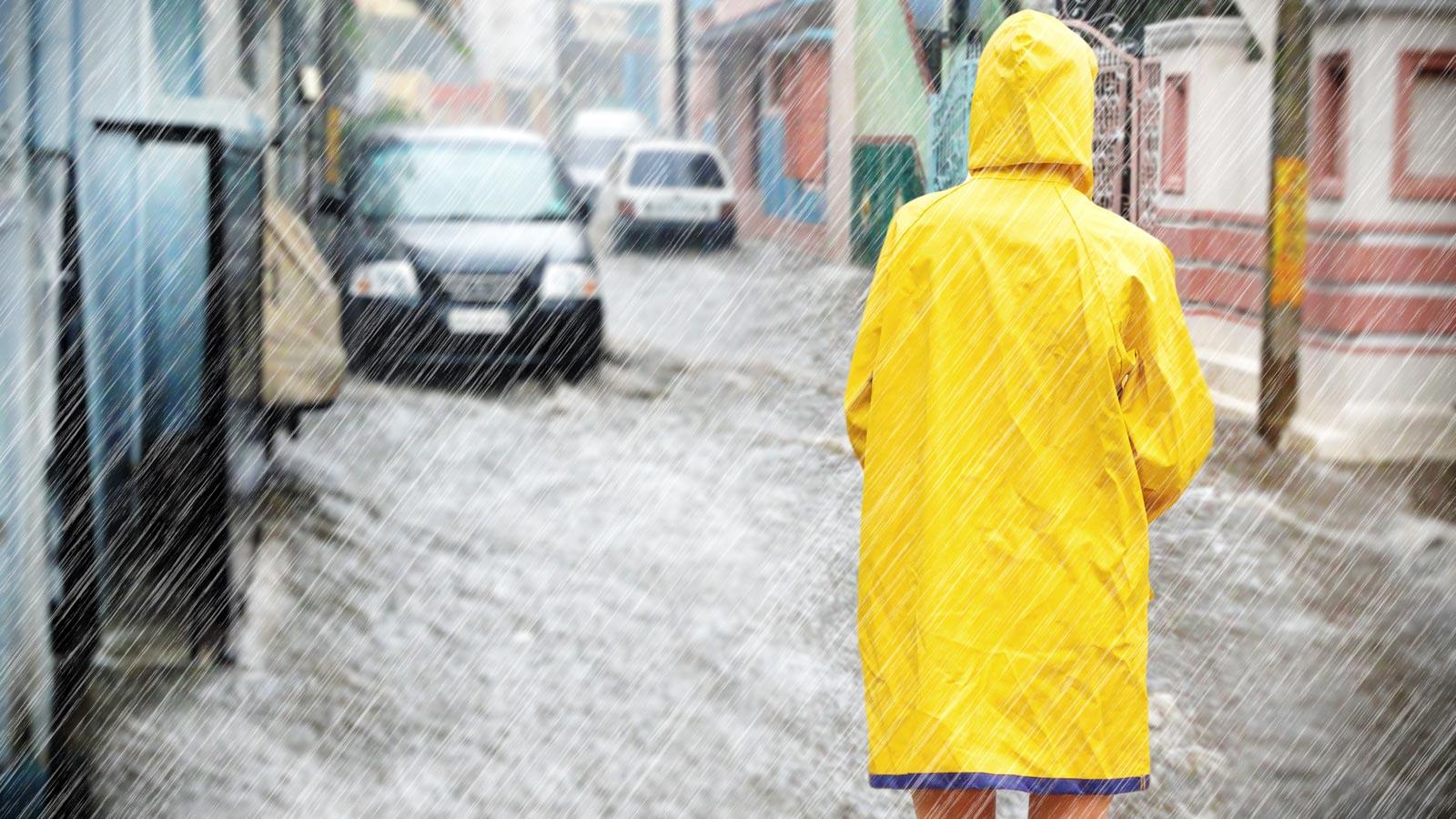Person mit gelbem Regenmantel steht in Starkregen und überschwemmter Straße it dem Rücken zum Betrachter iim
