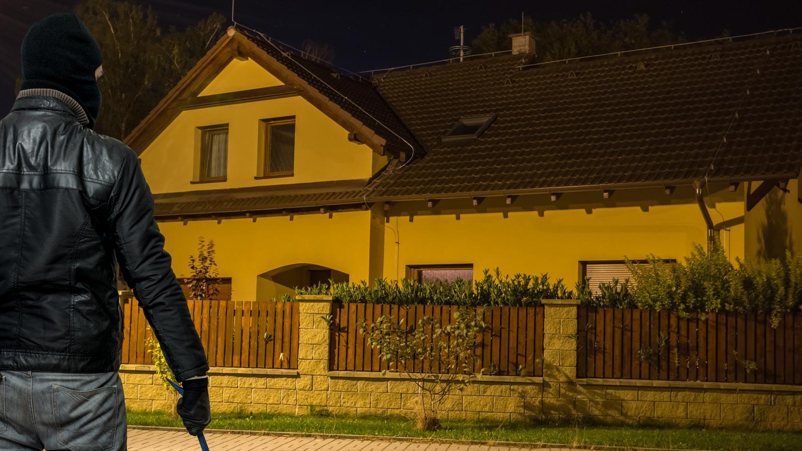 Vermummter Einbrecher steht nachts vor einem Haus