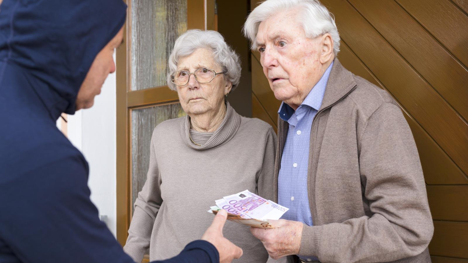 Seniorenpaar an der Haustür übergibt Bargeld an Betrüger