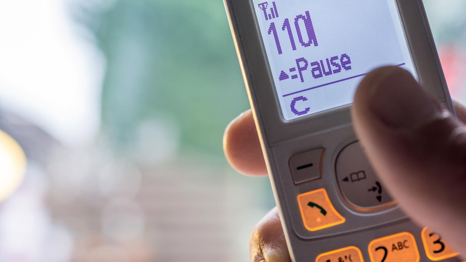 Mobiltelefon in Großaufnahme mit der Nummer 110 im Display