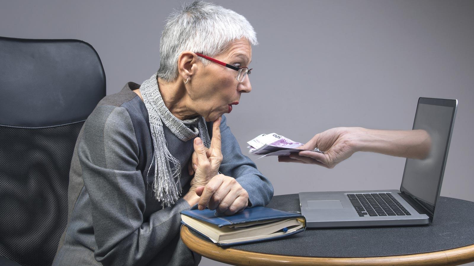 Ältere Frau vor einem Laptop, aus dem ein Arm mit einem Geldbündel herausragt.