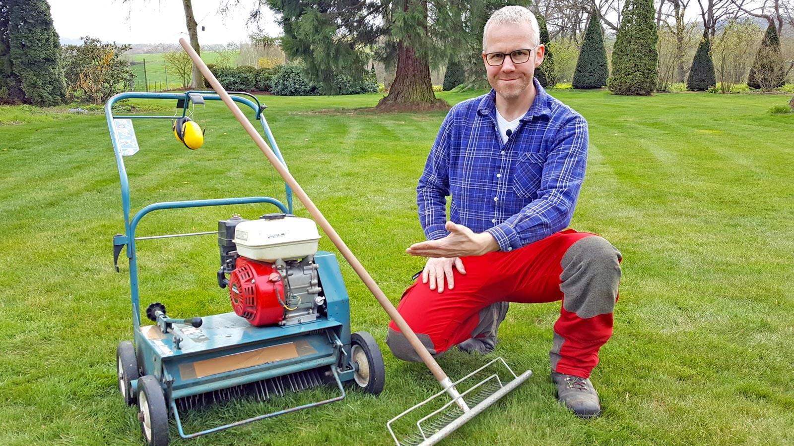 Gartenberater Philippe Dahlmann mit einem Vertikutiergerät und Harke auf einer Rasenfläche
