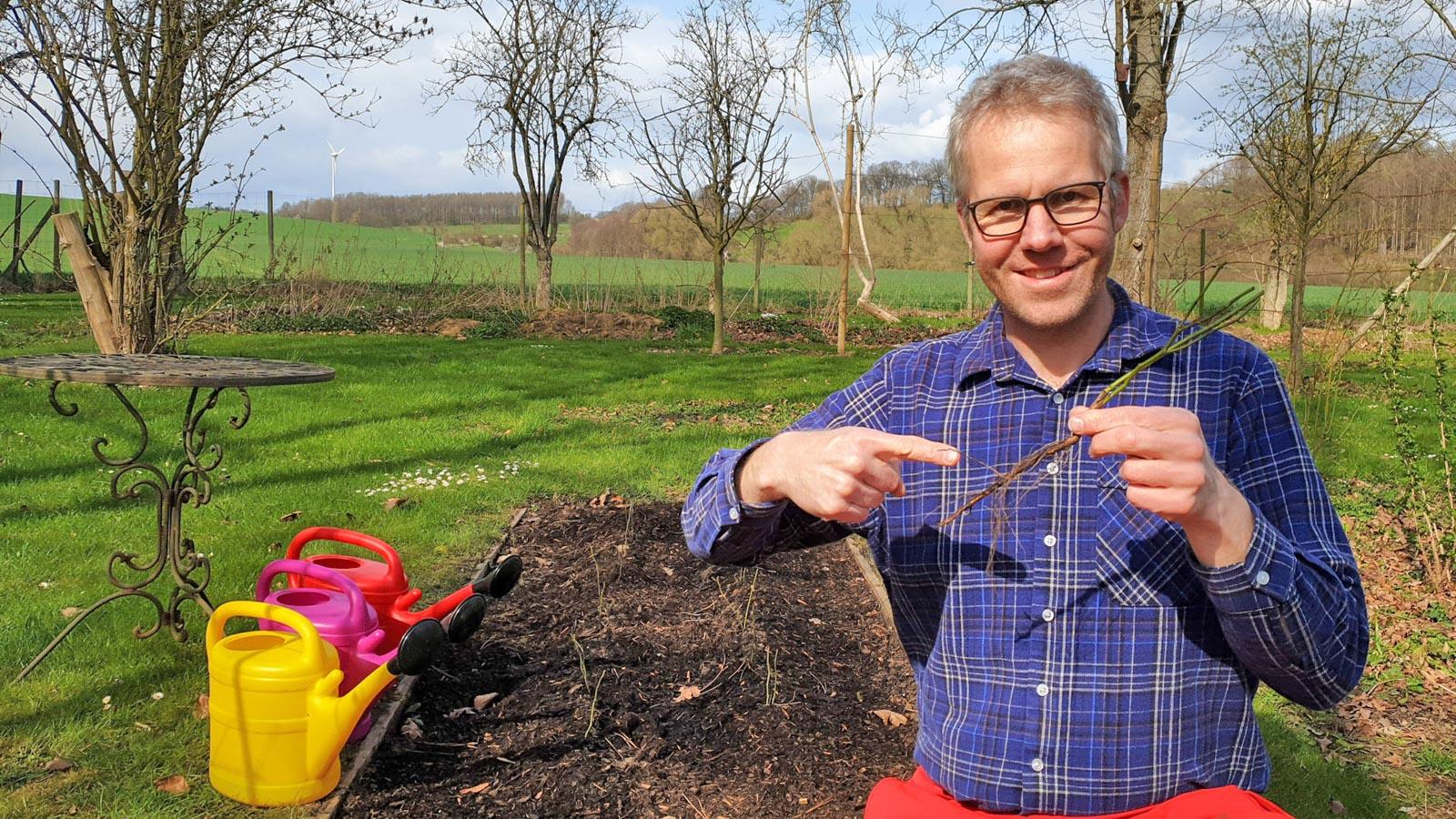 Gartenberater Philippe Dahlmann mit einer Veredelungsunterlage in der Hand vor einem Beet