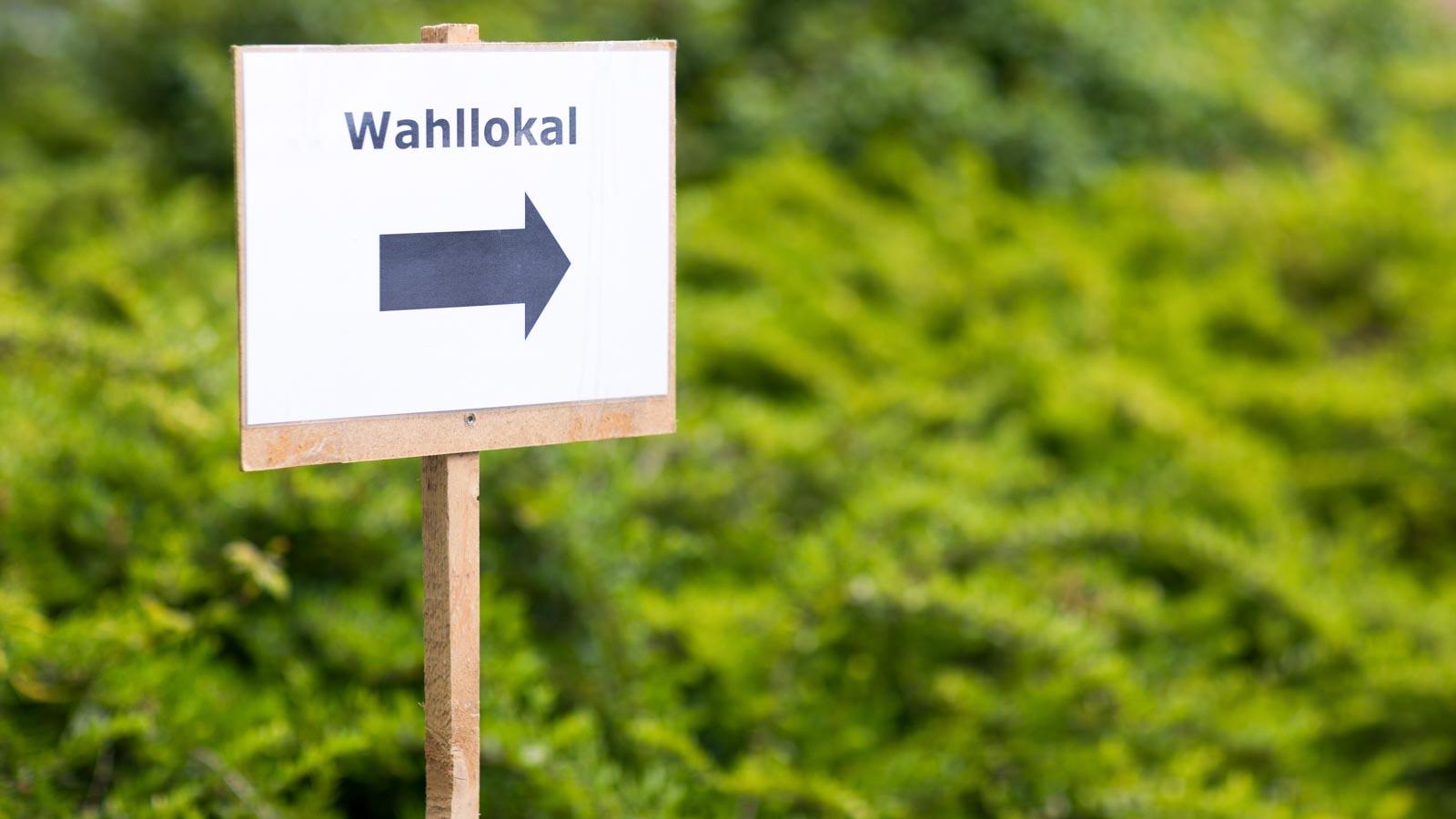 Schild mit einem Wegweiser zum Wahllokal