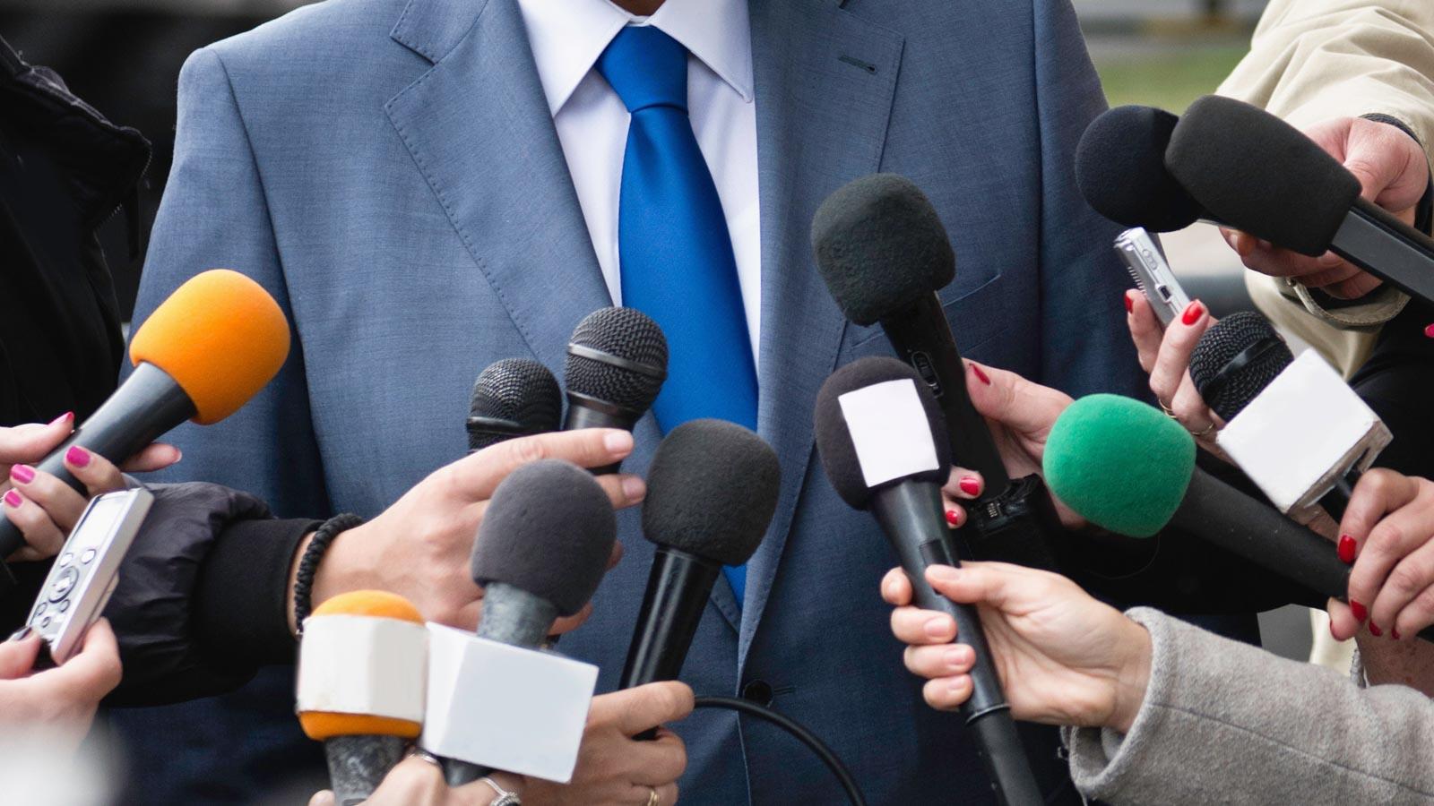 Reporter befragen Politiker. Ausschnittbild mit Mikrofonen.