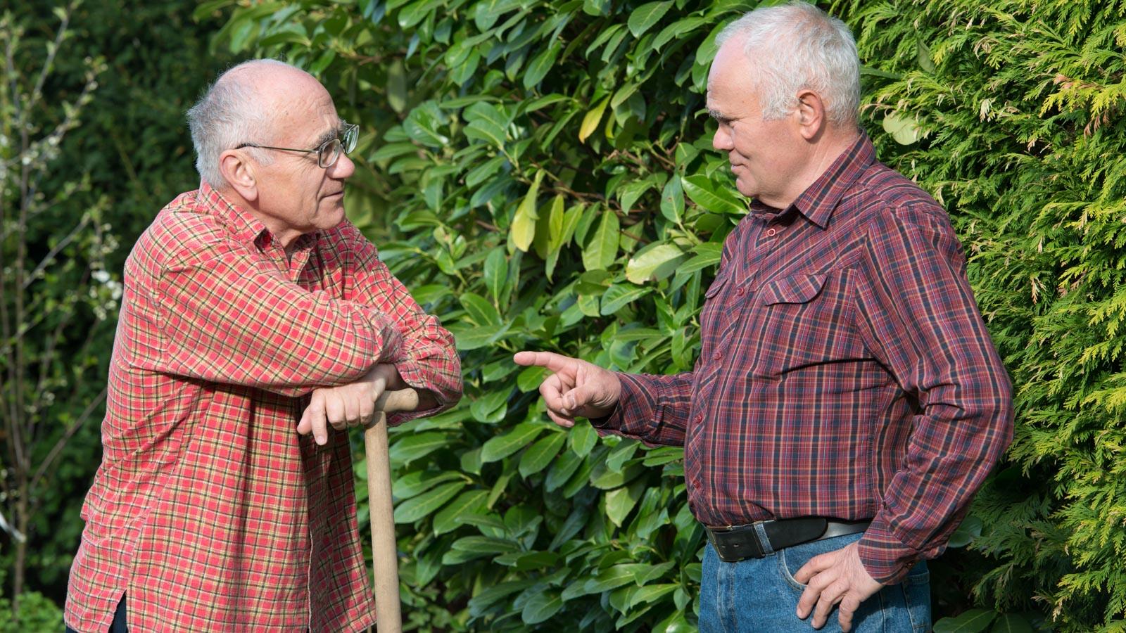 Zwei ältere Herren diskutieren im Garten