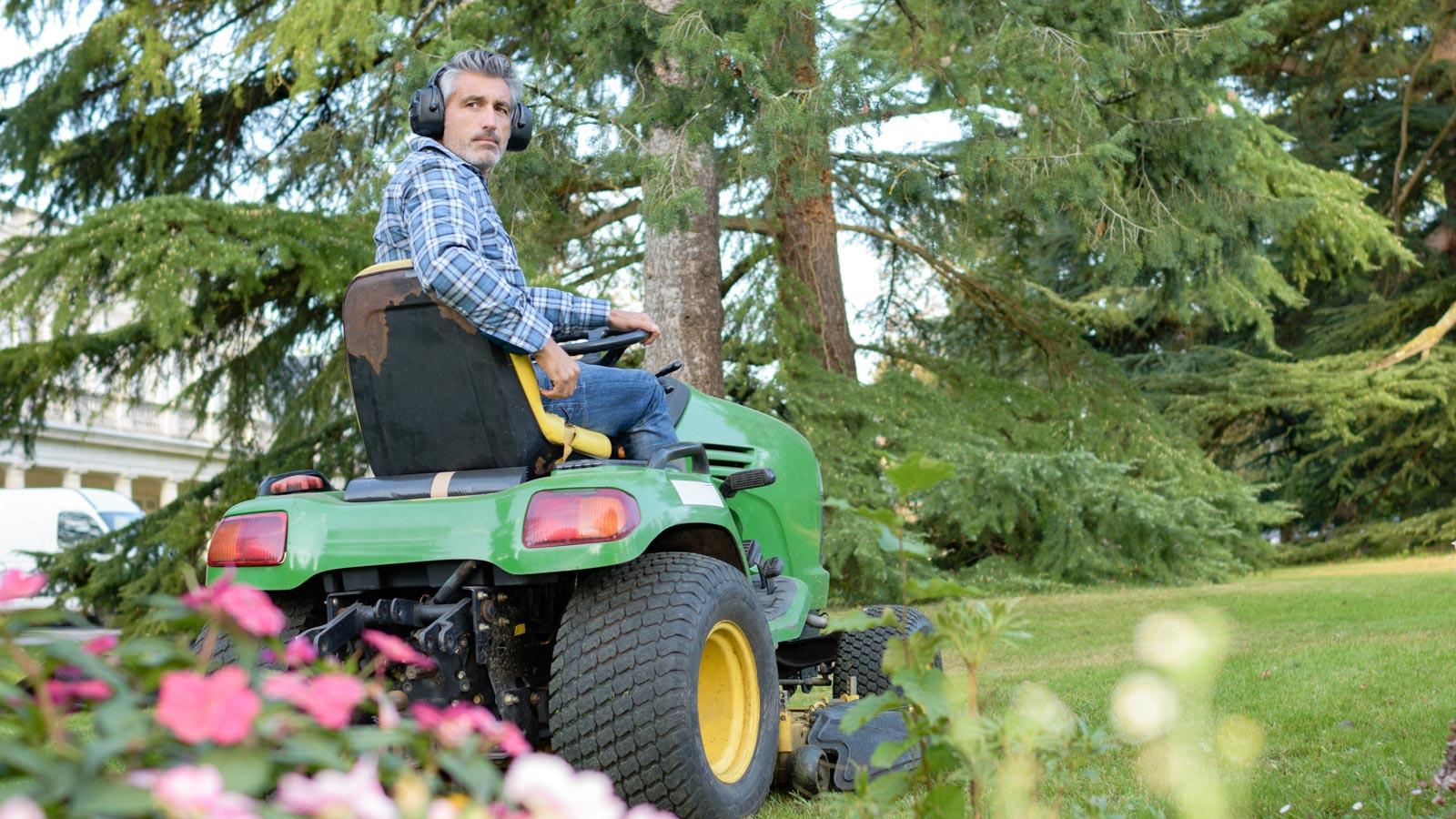 Mann auf einem Aufsitzrasenmäher im Garten