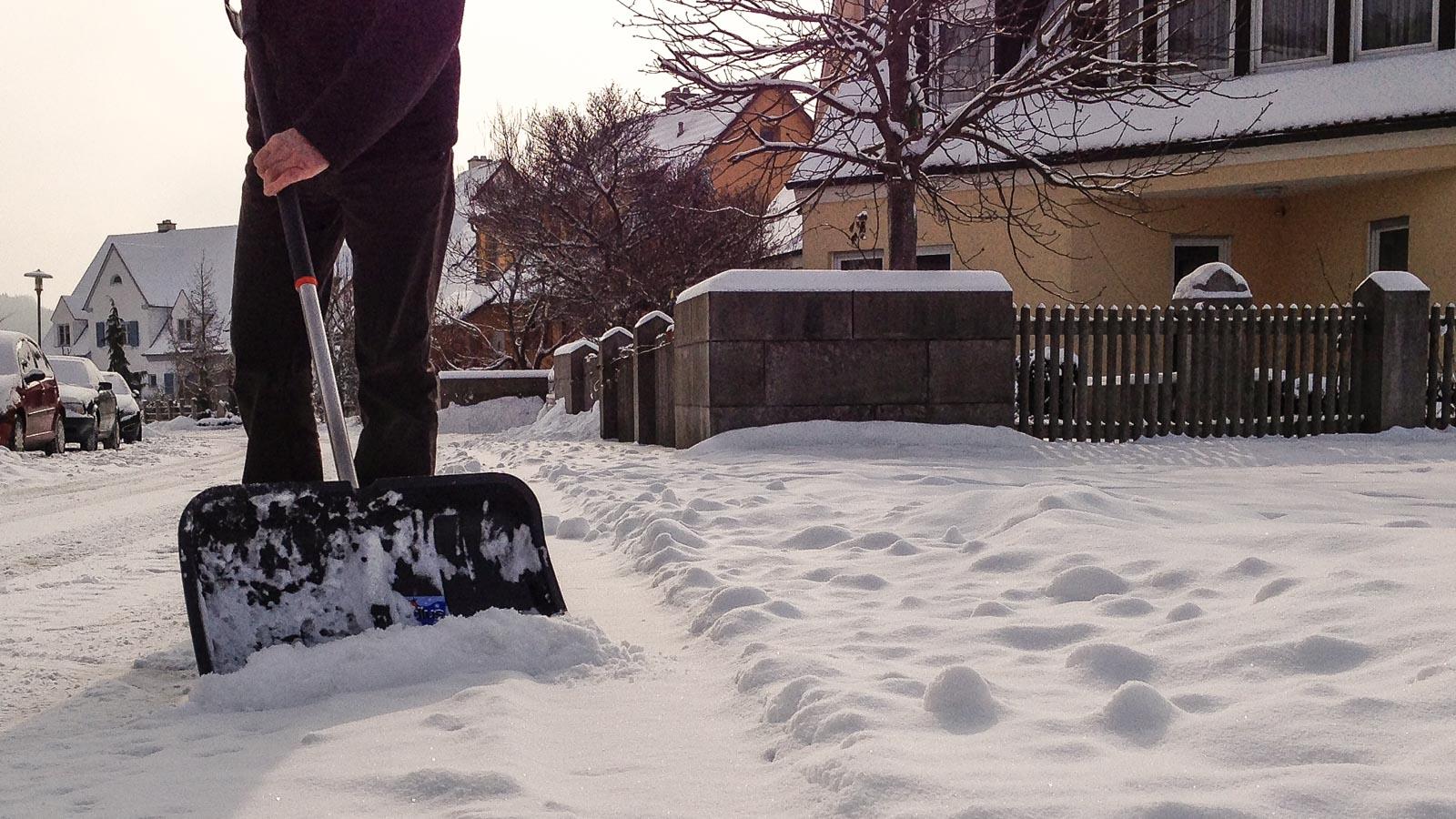 Mann beseitigt Schnee auf dem Bürgersteig mit Schneeschaufel