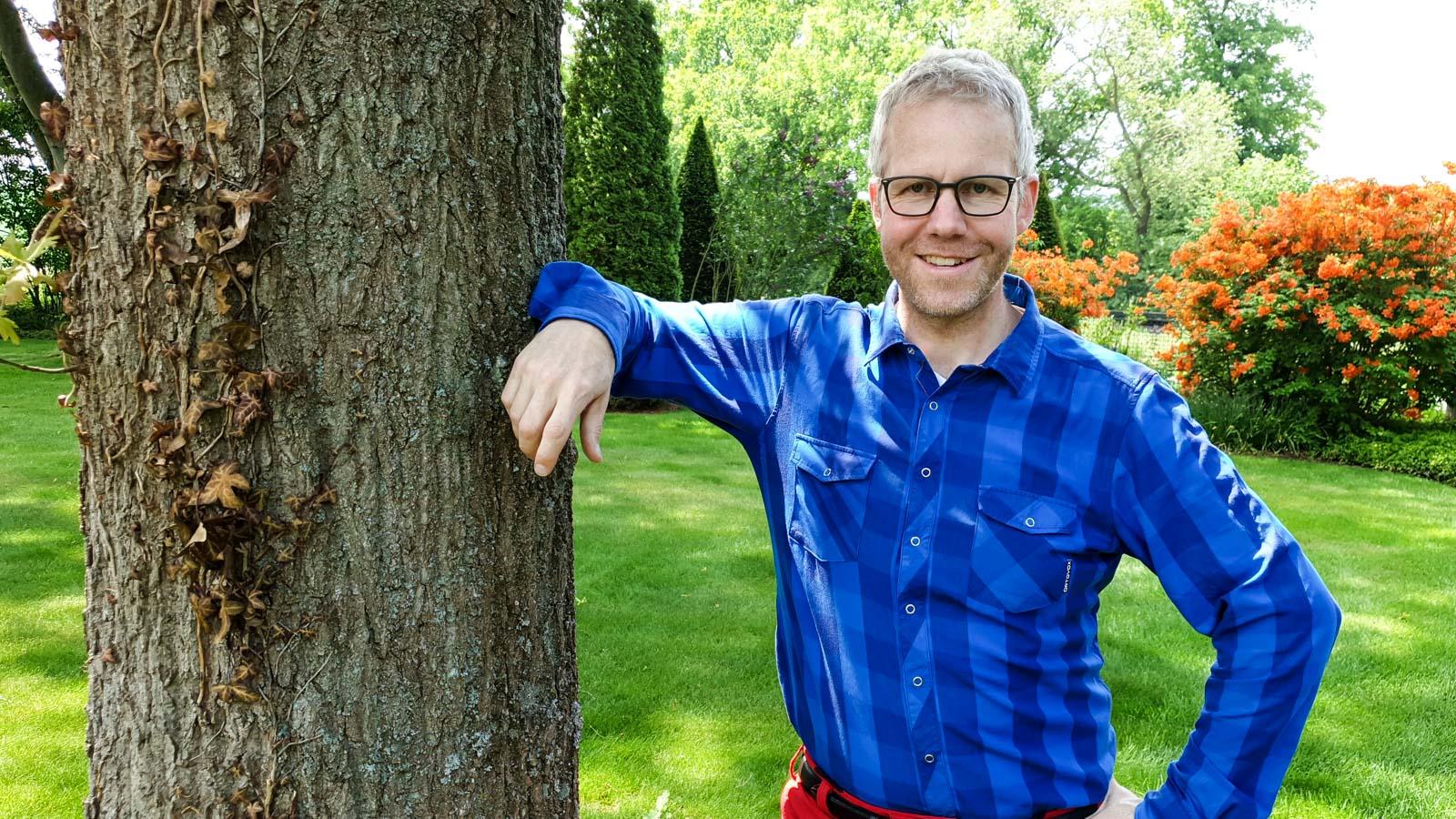 Philippe Dahlmann, Gartenberater vom Verband Wohneigentum, an einer Eiche stehend.