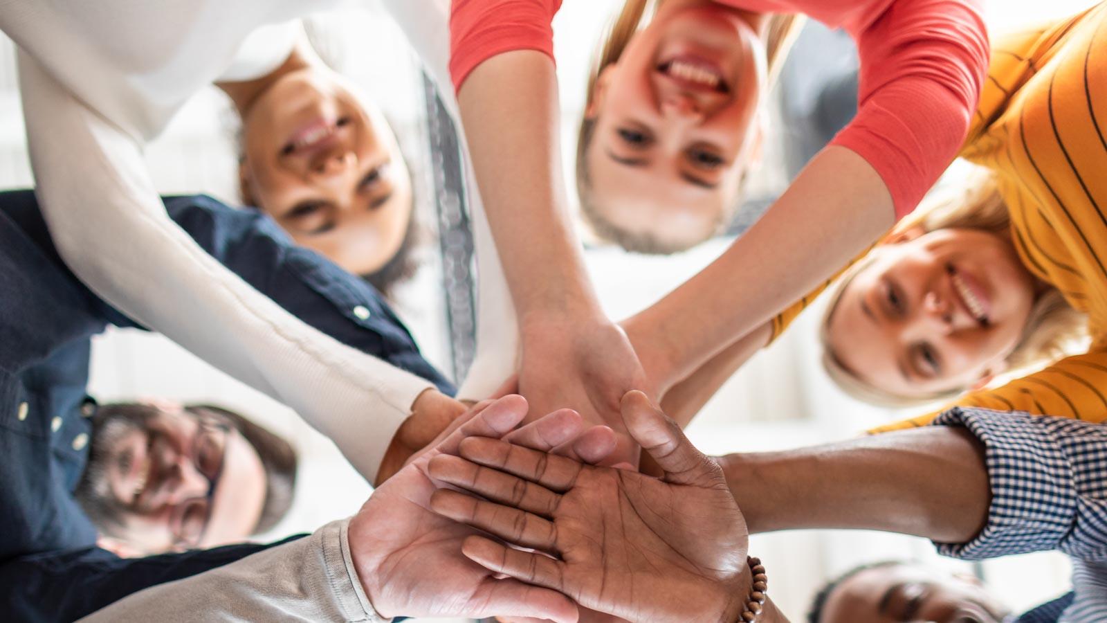 Kreis von Personen, die die Hände übereinander halten, von unten aufgenommen