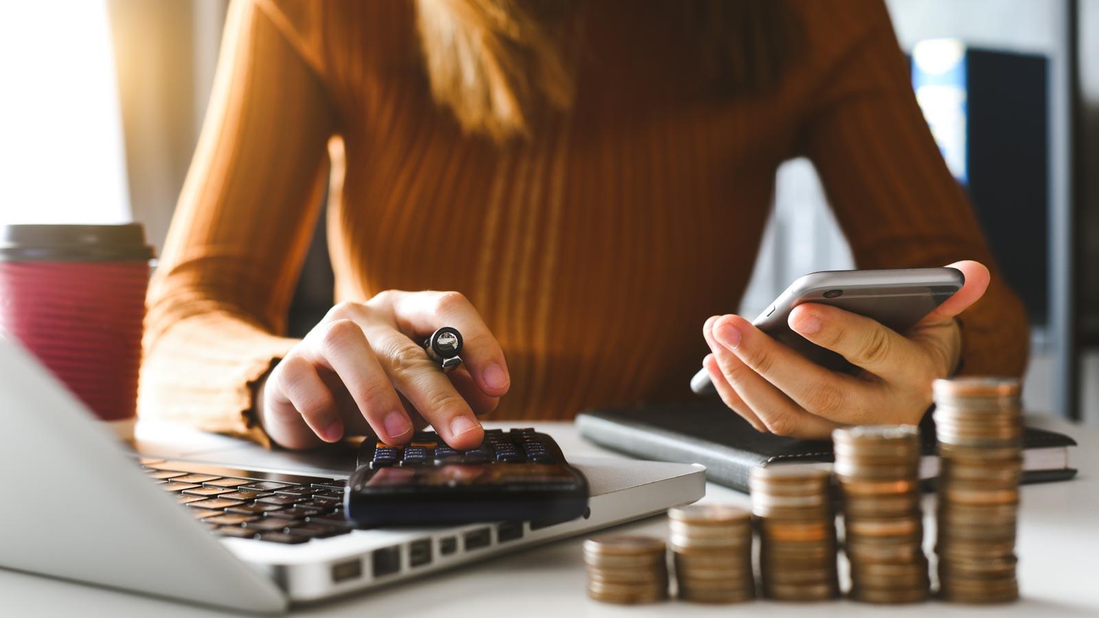 Junge Frau mit Handy, Taschenrechner und Laptop, im Vordergrund Münzstapel