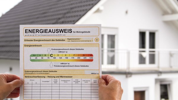 Hände halten Energieausweis ins Bild, im Hintergrund ein Haus